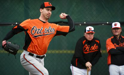 Orioles manager Buck Showalter and Rick Peterson, director of pitching development, watch Orioles pitcher Mark Hendrickson as he throws during the second day of workouts at at the team's spring training facility in Sarasota, Fla.