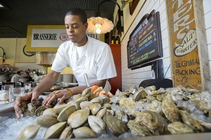 David Woodall arranges mussels and clams at the raw bar at Brasserie Brightwell in downtown Easton.