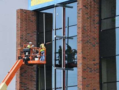 Workers add pieces of metal trim to a section of exterior windows Tuesday afternoon at the site of the Havre de Grace middle, high school building. The 250,111-square-foot school building is projected to open for the 2020 school year.