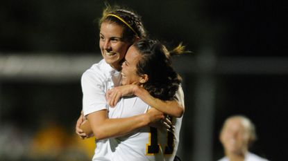 UMBC forward-midfielder Lilly Rydon jumps into the arms of forward Jessy Brown.