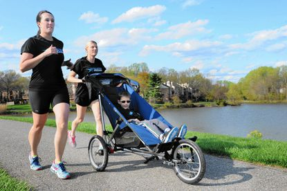 At Lake Elkhorn, Stephanie Blades, left, and Marie Vazquez take turns pushing Gabriel Vazquez, Marie's son, in a running stroller. Blades is an employee of the Community Action Council of Howard County and volunteers as a coordinator for Athletes Serving Athletes. She is training with Gabriel and his mom for the Columbia Half Marathon and 5K.