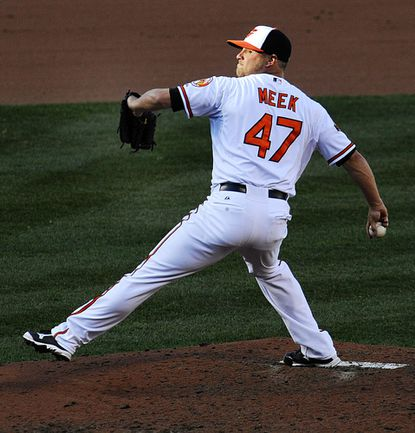 Evan Meek pitches during the Baltimore Orioles' 2-1 Opening Day win over the Boston Red Sox at Oriole Park at Camden Yards Monday, March 31, 2014.