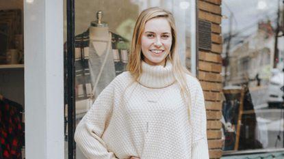 A retail associate at Primitive Beginnings models a new line.