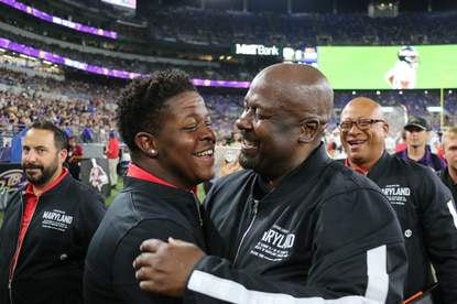 Maryland football coach Mike Locksley, right, awarded senior walk-on Bruce Miller, left, a scholarship at the Ravens' preseason game against the Green Bay Packers on Aug. 15, 2019, at M&T Bank Stadium. (Maryland Athletics)