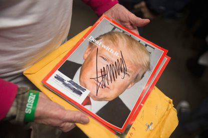 A supporter holds a copy of Time magazine he had signed by Republican presidential candidate Donald Trump during a rally at Des Moines Area Community College Newton Campus on November 19, 2015 in Newton, Iowa.