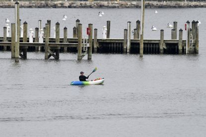 """A kayaker paddles past the Annapolis Yacht Club in Annapolis, Md., Tuesday, April 7, 2020. White recreational boating is prohibited under the coronavirus pandemic """"stay at home"""" order issued by Maryland Gov. Larry Hogan, kayaking and paddleboarding are permitted as long as social distancing and social gathering rules are followed since they are forms of exercise. The Annapolis Spring Sailboat Show was officially canceled due to the ongoing coronavirus pandemic. (AP Photo/Susan Walsh)"""