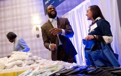 Two-time Super Bowl champion Torrey Smith, a former wide receiver for the Ravens and Maryland, laughs with Megan Waranch while putting together care packages for homeless people at the CareFirst BlueCross BlueShield annual CareFirst Commitment event in January in Annapolis.