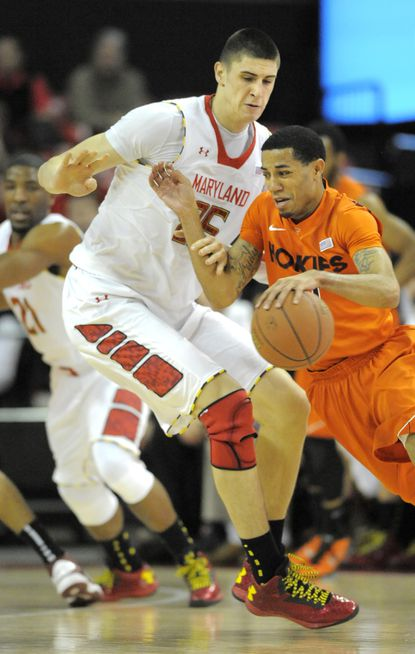 Terps center Alex Len, left, defends against Virginia Tech guard Erick Green in the first half at Comcast Center.