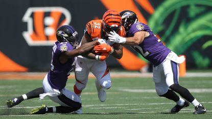 Tony Jefferson, left, and Eric Weddle combine to tackle Bengals running back Jeremy Hill in the season opener.