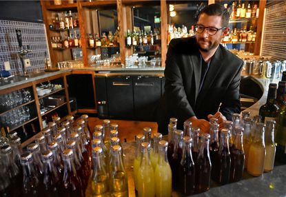 Paul Bankert, of the Bluebird Cocktail Room, organizes hand-mixed cocktails bottled for sale at The Pub, located below the Bluebird on Hickory Avenue in Hampden. Takeout food and liquor orders are a welcome option for beleaguered bar owners hit by the coronavirus, and official approvals to provide the service are being expedited.