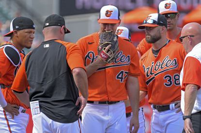Baltimore Orioles starting pitcher John Means (47) bites his glove while being patted by pitching coach/director of pitching Chris Holt (38) after being pulled for medical reasons against the Cleveland Indians during the first inning at Oriole Park at Camden Yards Sat., June 5, 2021. (Karl Merton Ferron/Baltimore Sun Staff)