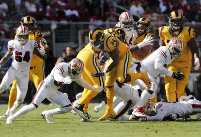 Rams running back Malcolm Brown (34) breaks though defenders as 49ers cornerback D.J. Reed (32) goes for the tackle at Levi's Stadium on Oct. 21.