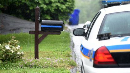 A Baltimore County Police officer sits in his car near the home of fellow officer Amy S. Caprio in Fallston Tuesday morning. Officer First Class Caprio was killed in the line of duty during an incident in the Perry Hall area Monday afternoon.