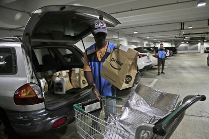 FILE - In this March 31, 2020, file photo, Samuel Diaz, a delivery worker for Amazon Prime, loads his vehicle with groceries from Whole Foods, in Miami, during the COVID-19 pandemic. A leap in U.S. unemployment has thrown a spotlight on one type of work still in high demand during the coronavirus pandemic: Gig work delivering groceries, meals and packages. (AP Photo/Lynne Sladky, File)
