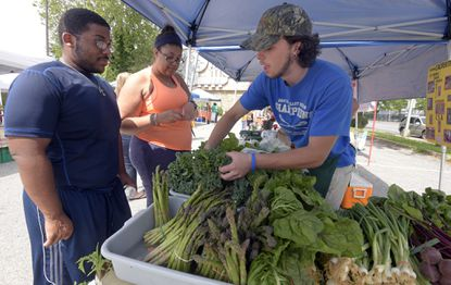 Collin Beck of Calvert Farm in Cecil County, right, gets greens for Joe Thomas, left, and Alex Jeffries at the Edmondson Viillage Farmers Market.