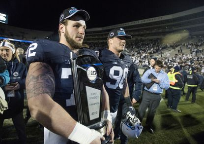 Penn State guard Brian Gaia carries the Big Ten East division trophy as the team celebrates their 45-12 win over Michigan State in State College, Pa., Saturday Nov. 26, 2016.
