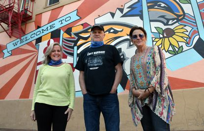 "From left, Jill Packo, owner of Barley's Backyard; Brian Recher, owner of The Recher, and Jackie McCusker, owner of Nacho Mama's, stand near the ""Welcome To Towson"" mural at York and Pennsylvania Avenue earlier this month."