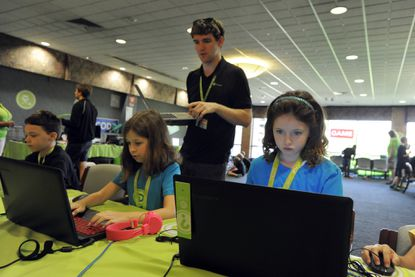 Henry Harrison, an instructor in the 3D Game Design area, helps (from left to right) Michael Mann,10, Annalee Nelson,11, and Madison Ackerman,10, with 3D game design in Minecraft.