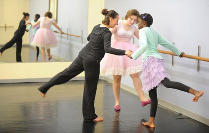 Dance/movement therapist Sarah Croushler, left, works with autistic students Noelle Wyatt, 11, right, and Rose McGuire, 15, both of Ellicott City, as they do exercises at the barre at Ballet Royale.