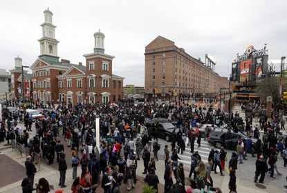 Protestors gather outside of Oriole Park at Camden Yards before a baseball game between the Boston Red Sox and the Baltimore Orioles after a rally for Freddie Gray, Saturday, April 25, 2015, in Baltimore. Gray died from spinal injuries about a week after he was arrested and transported in a police van.
