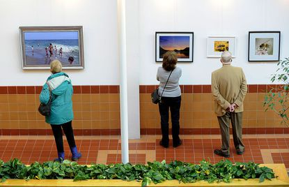 """Gail Holliday, Pat Scalice and Charles Shaffer look at works displayed in Carroll Community College's """"Con Artists"""" show, which features the work of the college's continuing education faculty, Sunday."""