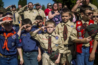 Boy Scouts and Cub Scouts salute during a Memorial Day ceremony in Linden, Mich.
