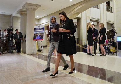 Rep.-elect Alexandria Ocasio-Cortez (D-N.Y.), right, with Rep.-elect IIhan Omar (D-Minn.), left, prior to a member-elect briefing on Capitol Hill in Washington.