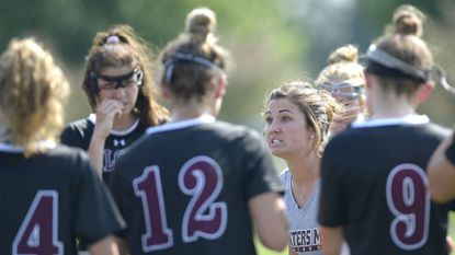 Winters Mill coach Amalie Meszaros talks to players during the second half, resumed from a lightning delay Monday, of their game against Century in Eldersburg on May 15, 2018.