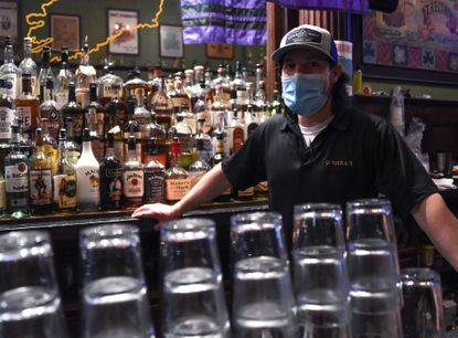 """""""It's tough having to enforce COVID laws and doing regular bartending on St. Patrick's Day,"""" said bartender Andrew Opiela, 30, who lives in East Baltimore. """"But we're happy to be open,"""" he added during a shift at Mick O'Shea's Irish Pub on Wednesday, March 10, 2021."""