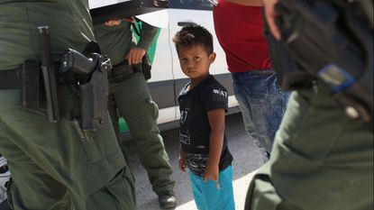 U.S. Border Patrol agents take into custody a father and son from Honduras near the U.S.-Mexico border on June 12, 2018 near Mission, Texas. The asylum seekers were then sent to a U.S. Customs and Border Protection processing center for possible separation.