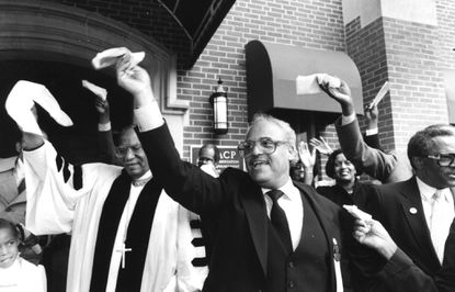 Baltimore's Democratic nominee for mayor, Brandon Scott, on Tuesday urged the NAACP to reconsider its move to Washington, D.C., given the organization's seasoned history in the city. In this 1986 photo, Benjamin L. Hooks and William E. Pollard lead a song at a celebration of what was then the NAACP's new headquarters in Baltimore.