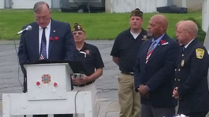 Deputy Secretary of the Maryland Department of Veterans Affairs Robert L. Finn speaks on Memorial Day in Union Bridge, at VFW Post 8806, in front of the VFW War Memorials, as Union Bridge Mayor Perry Jones and Commissioner Steve Wantz look on.