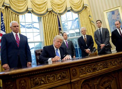 This file photo taken on January 23, 2017 shows US President Donald Trump signing an executive order alongside White House Chief of Staff Reince Priebus (C), US Vice President Mike Pence (L), National Trade Council Advisor Peter Navarro (3rd R), Senior Advisor Jared Kushner (2nd R) and Senior Policy Advisor Stephen Miller in the Oval Office of the White House in Washington, DC, January 23, 2017.