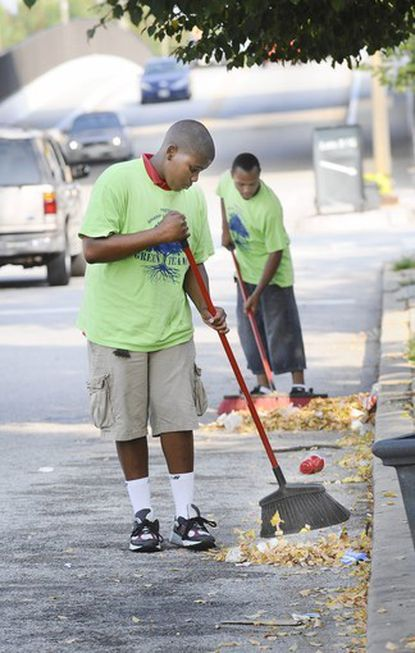 DaJuan Braxton, 15, says the litter on Hamburg Street is worse after a ball game, when game attendees throw trash in the street. In background Allen Haydel sweeps debris into a pile.