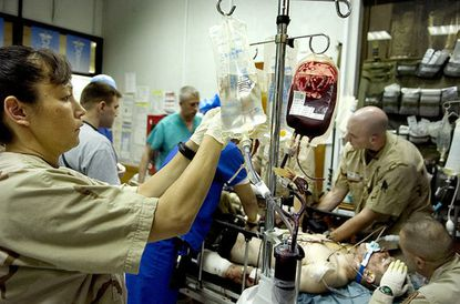 A nurse restocks a supply of blood and fluids as military doctors rush to give emergency care to a wounded soldier.
