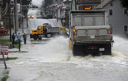 A county vehicle makes its way through flood waters covering Main Street in Union Bridge Oct. 30 following heavy rainfall associated with Hurricane Sandy.