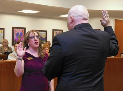 Ellicott City, MD. Kirsten Coombs is sworn in to the Howard County Board of Education by Wayne Robey, Clerk of the Court, during the Howard County School Board Meeting Monday night.