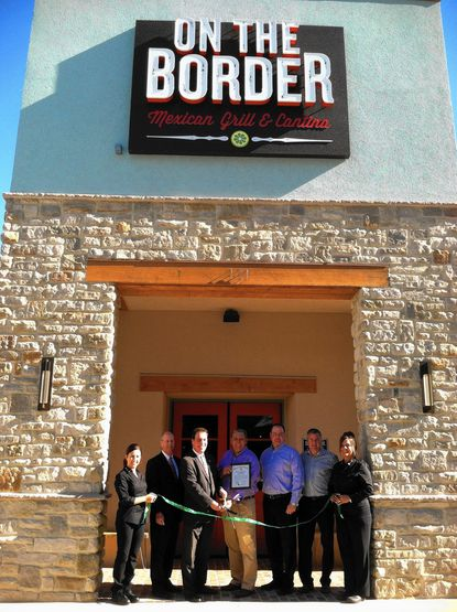 From left, Samantha David, of Detroit, John Holman, president of the Towson Chamber of Commerce, County Executive Kevin Kamenetz, Erik Skinner, regional director for On the Border, Mark Formwalt, general manager of the Towson restaurant, Devin Keil, senior vice president of development, and Lorna Leone, of Atlanta, cut the ribbon for On the Border Mexican Grill & Cantina on Monday. David and Leone are corporate trainers for the restaurant chain.