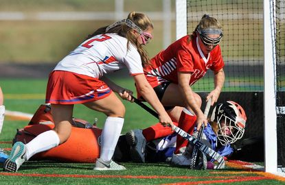 Roland Park Country School's Louisa Huber, center, scores against Centennial defender Bella Brillante, left, and goalkeeper Jenna Dietrich in the Reds' 4-0 victory Tuesday in Ellicott City.