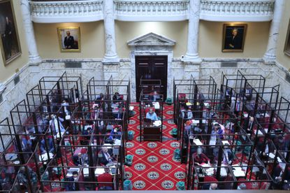The Maryland Senate meets on the last day of the state's 90-day legislative session on Monday, April 12, 2021 in Annapolis. Senators have been working inside enclosures around their desks as a precaution during the COVID-19 pandemic. (AP Photo/Brian Witte)