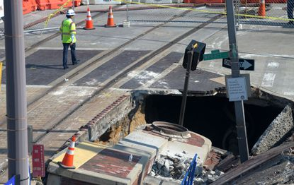 A contractor with KCI walks past a sinkhole at Pratt and Howard Streets in Baltimore following a water main break last summer.