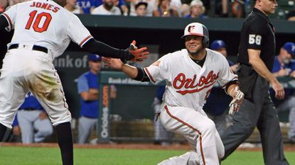 The Orioles' Welington Castillo, right, celebrates with teammate Adam Jones after scoring during a game in July.