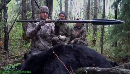 Josh Bowmar, seen here at left in a still image made from video, displays the spear with which he killed a large black bear, which resulted in a public backlash. (Still from YouTube) - Original Credit: