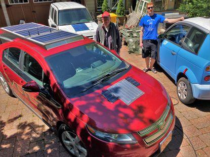 "Bob Bruninga, center, with ""FrankenVolt,"" his 2013 solar-enhanced Chevrolet Volt plug-in hybrid car. His son, AJ, drives the electric Th!nk, on the right."