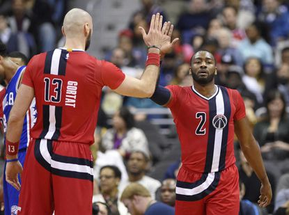 Wizards guard John Wall (2) reacts with center Marcin Gortat (13), of Poland, during the first half of an NBA basketball game against the Philadelphia 76ers, Saturday, Jan. 14, 2017, in Washington.