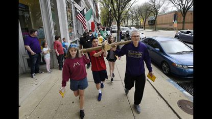 From left, Nancy Suder of Hampstead, David Ripper of Westminster, Kyra King of Taneytown and Delmas Wood of Westminster carry a wooden cross down East Main Street in Westminster as they lead the 2019 Good Friday Community Cross Walk April 19, 2019.