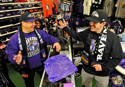 "Chris ""C-Dog"" Dressel of Parkville, a Ravens rapper, left, high-fives store manager Kenny Yates at The Ravens Zone."