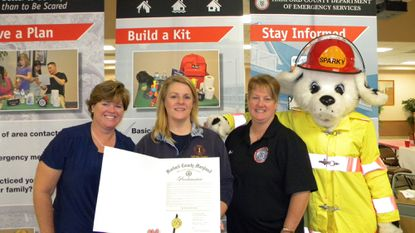 Melissa Blessing, left, of the Harford County Department of Emergency Services presents a County Executive Proclamation to Assistant Chief Rhonda Hinch of the Level Volunteer Fire Company with Kim Stritzinger, a Public Safety Dispatcher III and Sparky looking on. Harford fire companies are observing Fire Prevention Week this week, with several like Level holding open houses this past weekend and several others opening their doors this weekend.