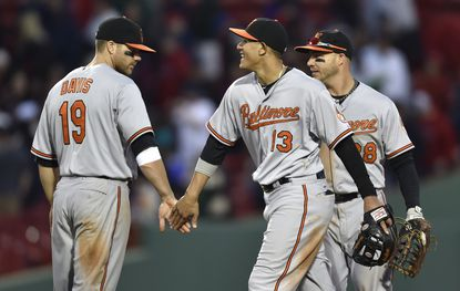 TheOrioles, including Manny Machado (13), Chris Davis (19) and Steve Pearce (28), celebrate their 4-1 win over the Boston Red Sox, Saturday, April 18, 2015, in Boston.