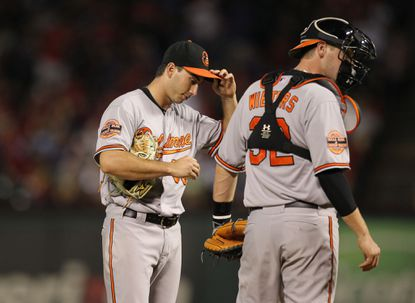 Miguel Gonzalez reacts with catcher Matt Wieters after giving up a run in the fifth inning Monday.